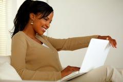 微笑和查找对膝上型计算机的可爱的黑人妇女 免版税库存图片