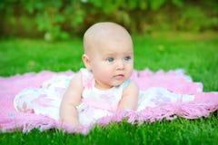 微笑和查寻对照相机的婴孩户外在阳光 库存照片