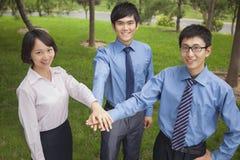 微笑和汇集他们的手的商人作为队工作和欢呼的标志 免版税库存照片