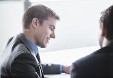 微笑和注视着下来业务会议的两个商人 免版税库存图片