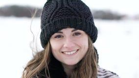 微笑和注视着对照相机的可爱的女孩有风冷的冬日 股票视频