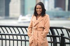 微笑和看在照相机佩带的开士米夹克的美丽的非裔美国人的妇女在冷的冬天城市 免版税库存图片