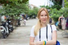 微笑和看在街道上的快乐的少妇照相机 免版税图库摄影