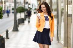 微笑和看她的智能手机的年轻深色的妇女 免版税库存图片