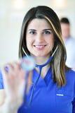 微笑和看对照相机的妇女医生,当一个医疗队工作时 免版税图库摄影
