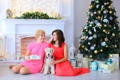 微笑和看彼此和sittin的女儿和母亲 免版税库存图片