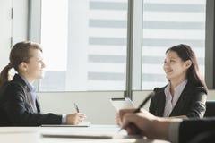 微笑和看彼此的两名女实业家在业务会议期间 库存照片