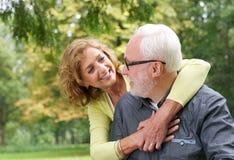 微笑和看彼此的愉快的更旧的夫妇户外 免版税库存图片