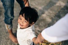 微笑和看照相机的愉快的年轻亚裔男孩,当握父母手时 免版税图库摄影
