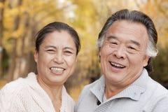 微笑和看照相机的老夫妇在公园 免版税库存图片