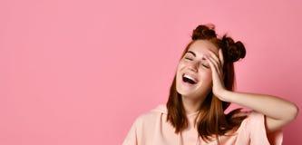 微笑和看照相机,闭合的眼睛的年轻愉快的妇女画象用手 免版税图库摄影