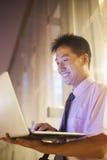 微笑和看他的膝上型计算机的年轻商人户外在晚上 库存图片