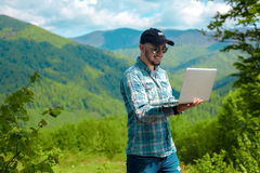 微笑和研究在山的膝上型计算机的人 免版税库存图片