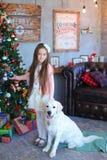 微笑和站立与狗的女孩在C的明亮的演播室 免版税库存图片
