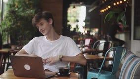 微笑和笑在咖啡馆、自由职业者和博客作者的年轻欧洲人有室内滑稽的闲谈,现代通信 股票录像