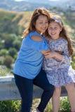 微笑和笑在黄色花前面的小山的拉提纳母亲和女儿 免版税库存照片
