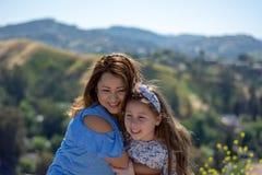 微笑和笑在黄色花前面的小山的拉提纳母亲和女儿 库存图片