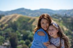 微笑和笑在黄色花前面的小山的拉提纳母亲和女儿 免版税图库摄影