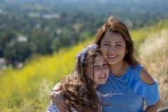 微笑和笑在黄色花前面的小山的拉提纳母亲和女儿 图库摄影