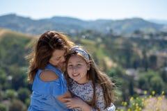 微笑和笑在黄色花前面的小山的拉提纳母亲和女儿 库存照片