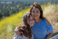 微笑和笑在黄色花前面的小山的拉提纳母亲和女儿 免版税库存图片