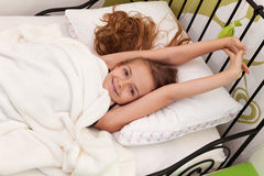 微笑和舒展在一个美好的早晨的女孩 免版税图库摄影