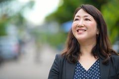 微笑和认为在街道的成熟愉快的美丽的亚裔女实业家户外 库存图片