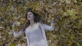 微笑和说谎在秋叶的地面上的美丽的式样女孩在慢动作的公园- 股票视频