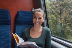 微笑和读书的年轻逗人喜爱的妇女,当旅行乘火车时 免版税库存照片
