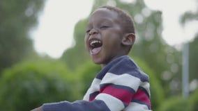 微笑和调查照相机的一个非裔美国人的孩子的画象 使用dorable的小男孩户外 股票录像