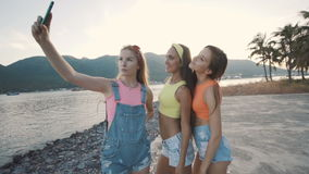 微笑和采取与一个巧妙的电话的三个朋友妇女selfie在海滩 股票视频