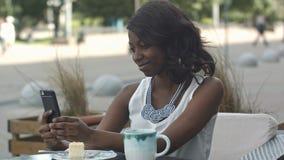 微笑和采取与她的智能手机的可爱的年轻非洲妇女一selfie,当单独坐在室外咖啡馆时 免版税库存照片