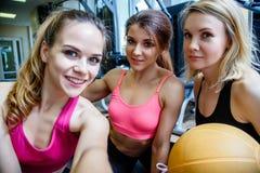 微笑和采取selfie的小组妇女在健身房 免版税库存照片