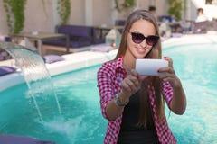 微笑和采取selfie的逗人喜爱的青少年的女孩 库存图片