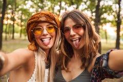 微笑和采取selfie wh的两名时髦的嬉皮妇女照片 库存照片