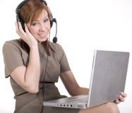 微笑和键入在膝部上面的俏丽的电话操作员画象  免版税库存图片