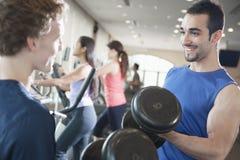 微笑和练习在健身房的两个年轻人举重 库存图片