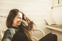 微笑在一个供以座位的房子里的妇女的画象 库存图片
