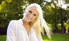 微笑在一个晴天的新美丽的妇女 免版税库存图片