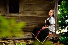 微笑在一个老房子的门廊的年轻罗马尼亚女孩 免版税库存图片