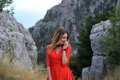 微笑在一件长的猩红色礼服的妇女在山的一个森林里 库存图片