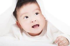 微笑在一块白色毯子或毛巾下的逗人喜爱的婴孩 库存图片