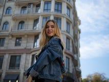 微笑在一现代大厦和天空蔚蓝的背景的一件牛仔布夹克的可爱的白肤金发的女孩 库存图片