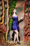 微笑在一件蓝色礼服的美丽的女孩在夏天公园 免版税库存图片