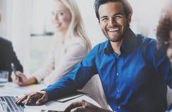 微笑在与伙伴的业务会议的成功的西班牙商人画象在现代办公室 水平 免版税图库摄影