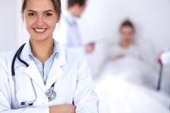微笑在与患者的背景的女性医生在床上 库存图片