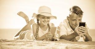 微笑在与电话的海滩哄骗在手上 库存照片