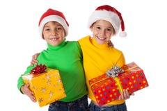 微笑在与礼物盒的圣诞老人帽子开玩笑 免版税库存照片