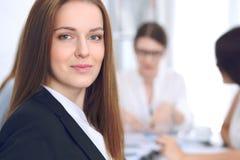 微笑在会议上的美丽的女商人在办公室 免版税库存图片