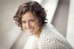 微笑在公园的一名俏丽的妇女的画象 免版税库存图片